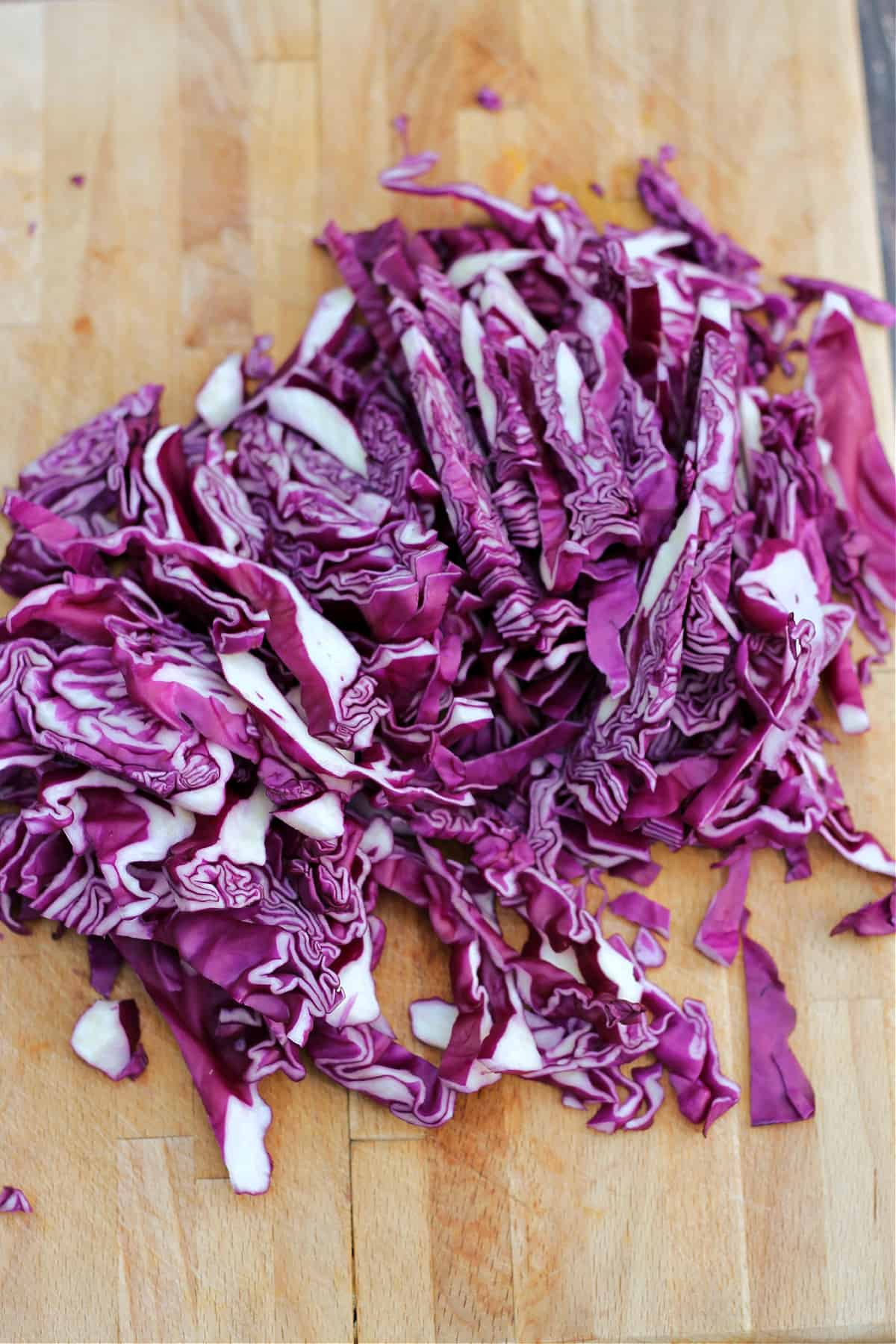 Finely shredded red cabbage on a wooden chopping board.