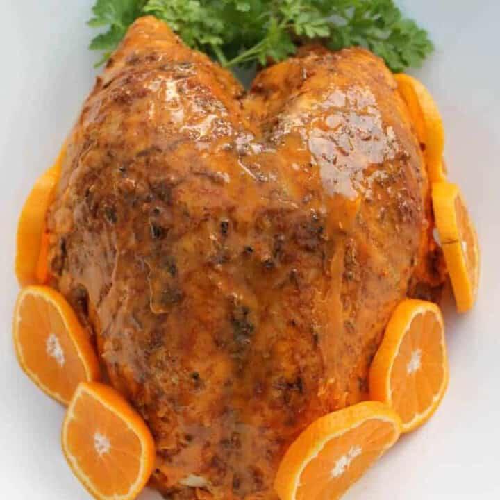 Turkey in serving dish with orange slices.