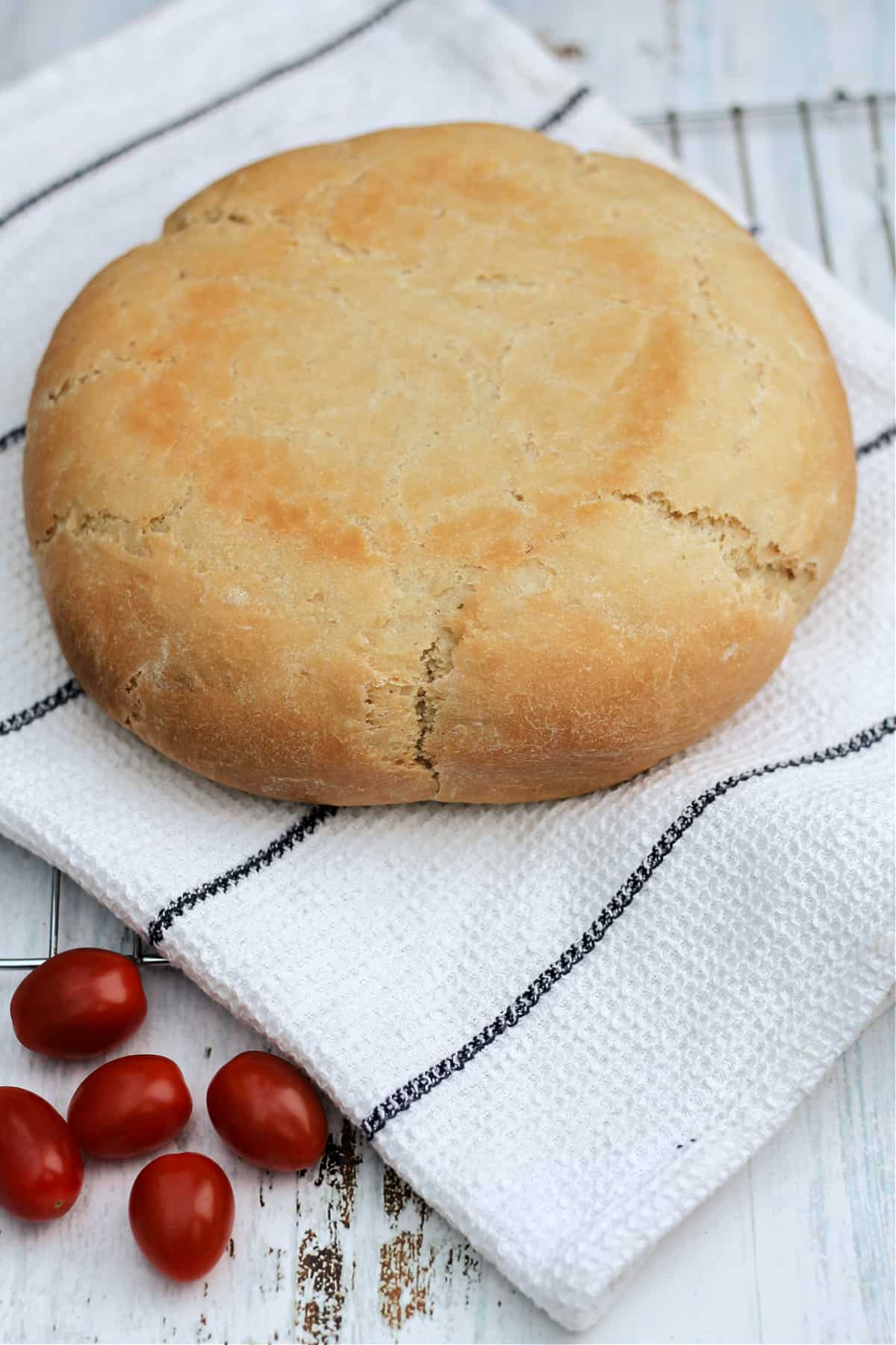 A round white loaf on a white striped cloth, with plum tomatoes on the side.
