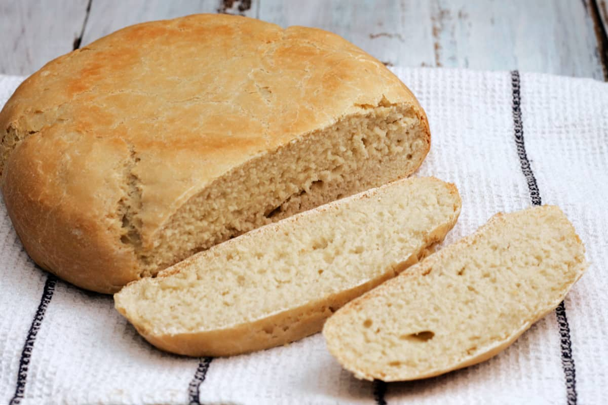Side view of round white loaf with two slices cut out.