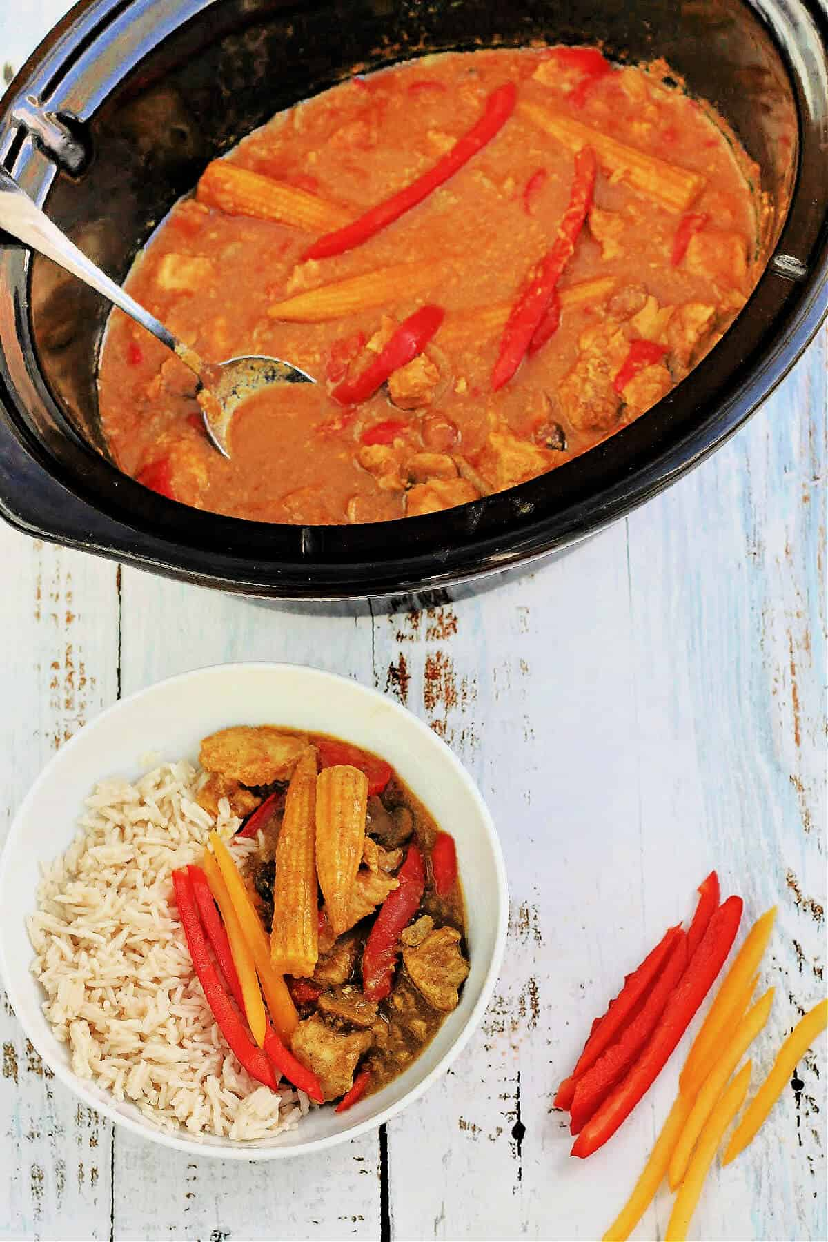 Slow cooker pot serving out Chinese curry with a bowl of curry and rice below.