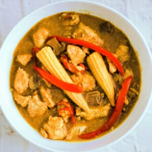 White dish with Chinese chicken curry with baby corn and red pepper.