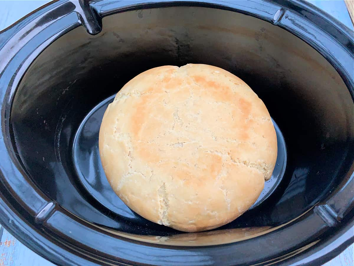 Baked round loaf of bread in slow cooker pot.