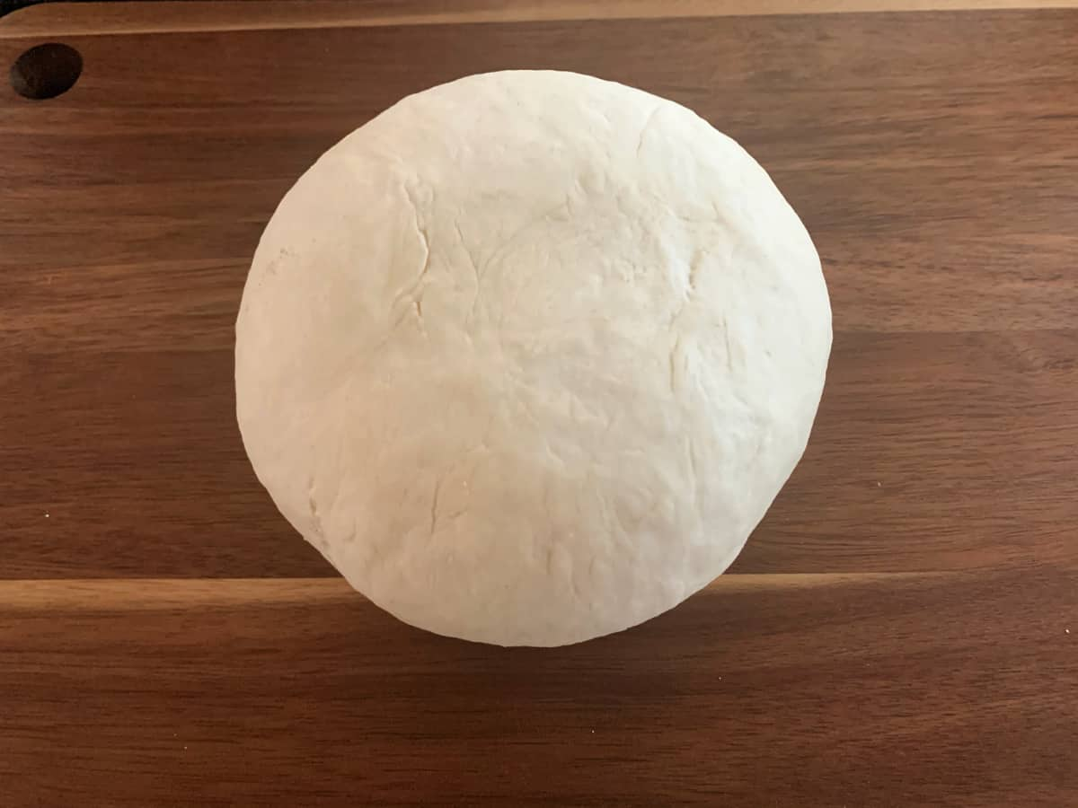 Ball of dough on a wooden board.