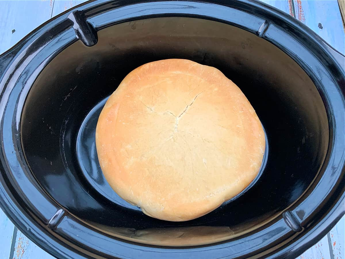 Bread with brown bottom in slow cooker pot, flipped over so the base is at the top.