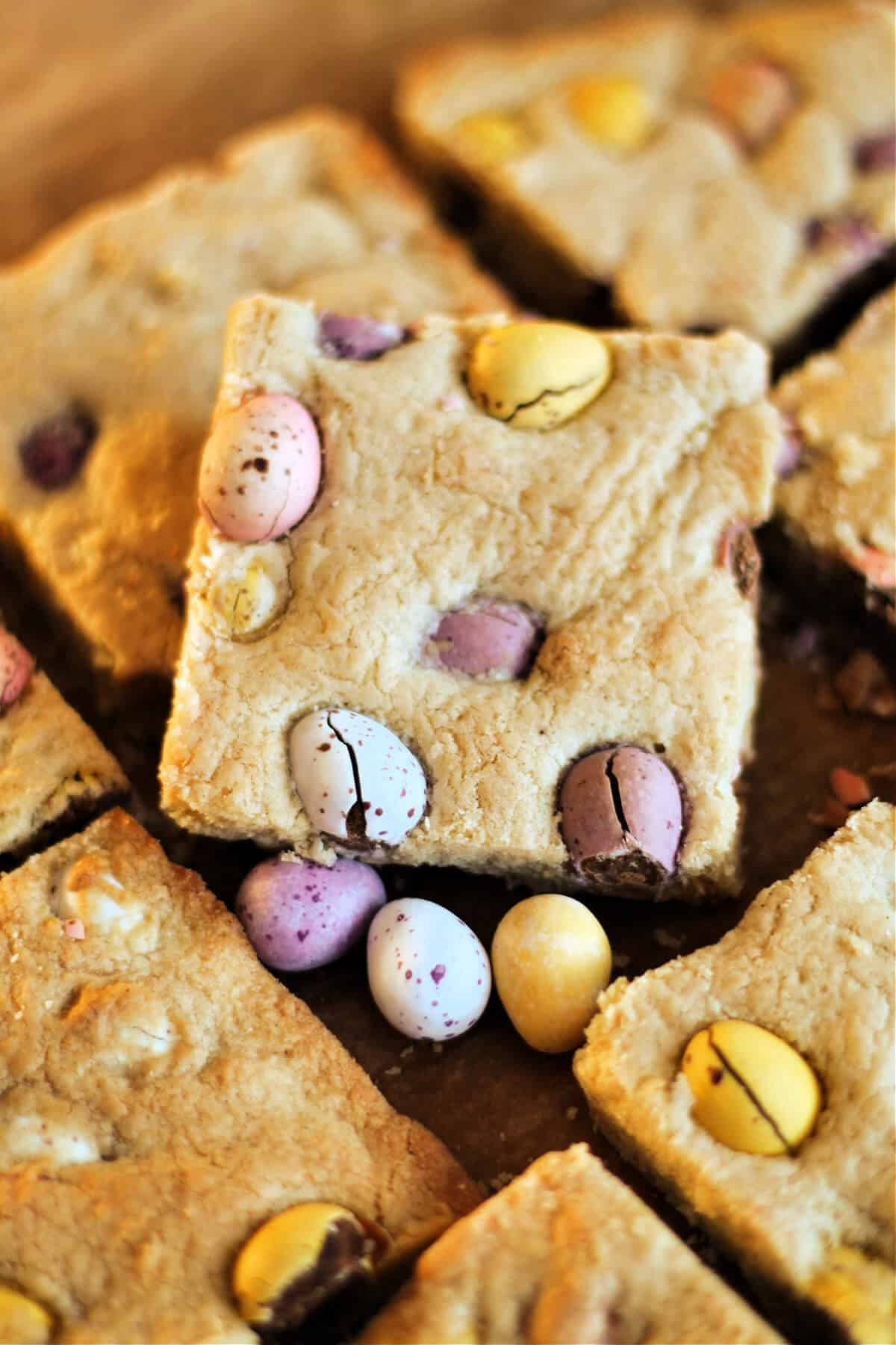 Cookie traybake with mini egg cut into squares.