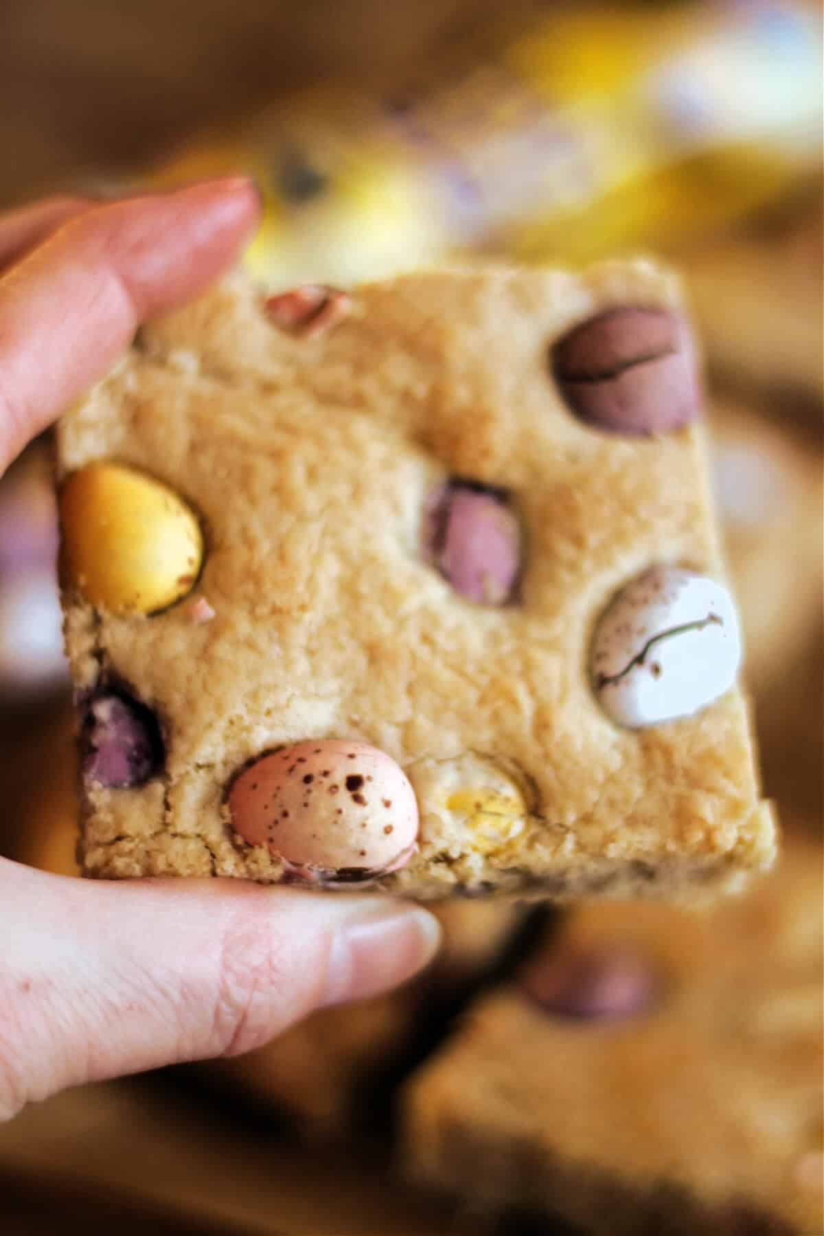 Hand holding a square cookie bar studded with chocolate mini eggs