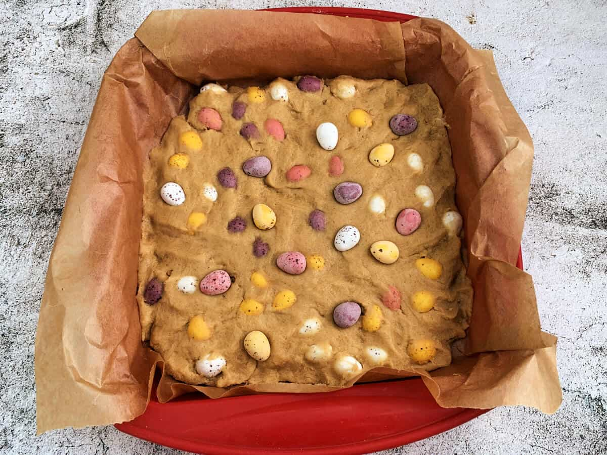 Mini egg cookie dough in square pan.