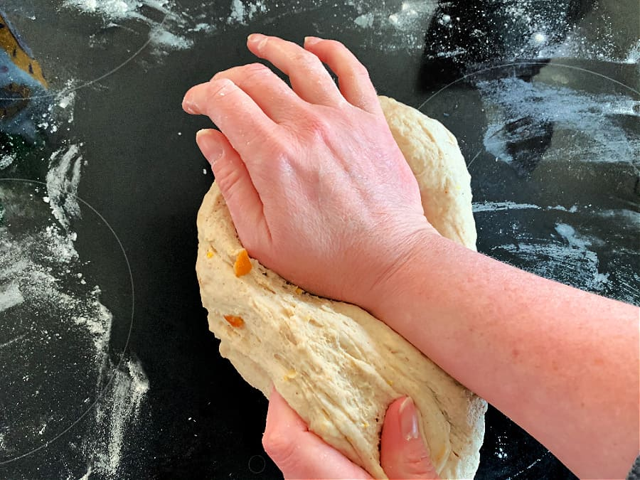 Kneading technique shown with the heel of the hand pushing the dough away.