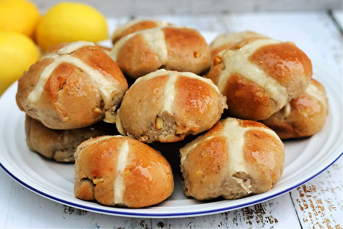 A pile of hot cross buns on a white plate.