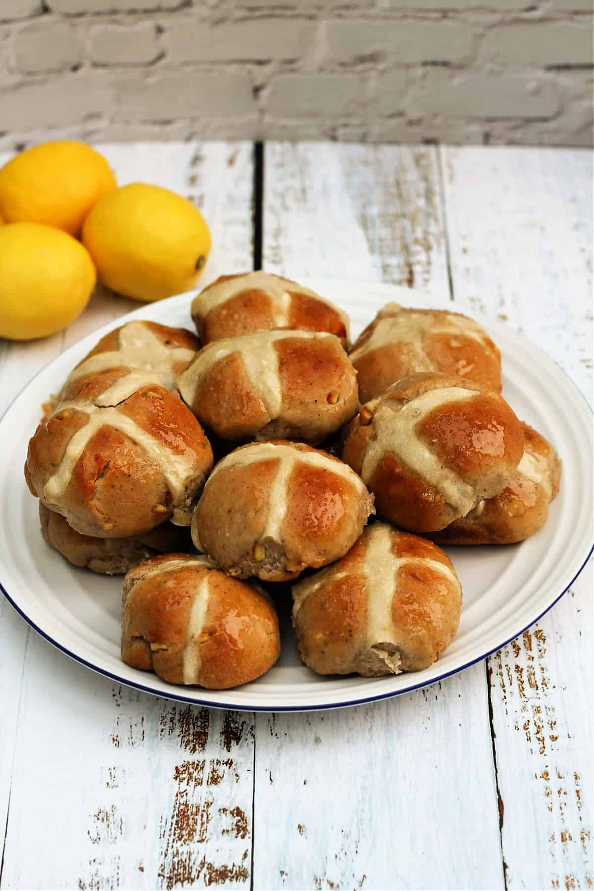 A white plate of hot cross buns, with lemons in the background.