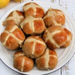 Close up of hot cross buns on a white plate.