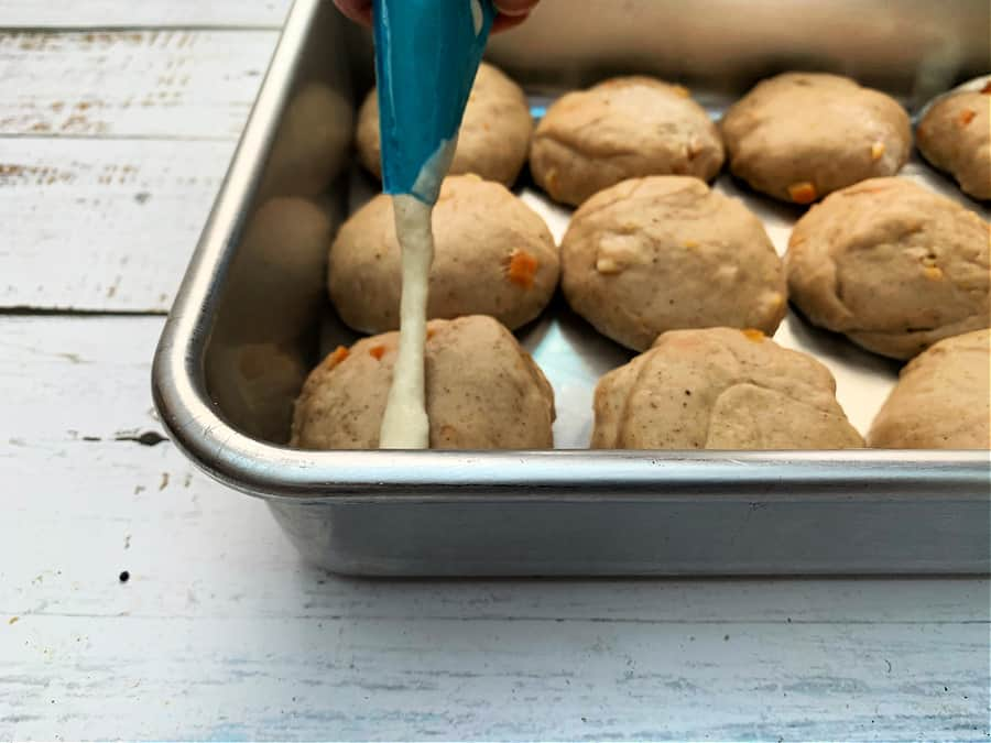 Piping crosses on hot cross buns in a baking pan using a piping bag.
