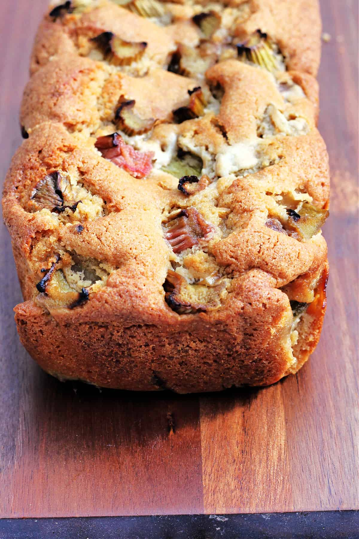 Close up of a fruit filled loaf cake on a wooden board.