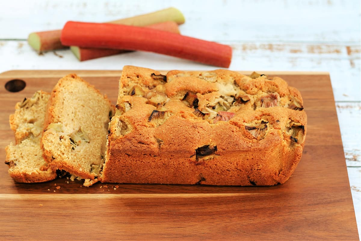 A loaf cake on a wooden board with pieces of rhubarb in the background.