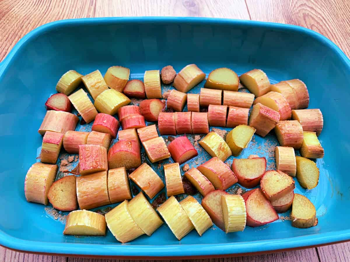Roasted rhubarb pieces in a blue ceramic dish.