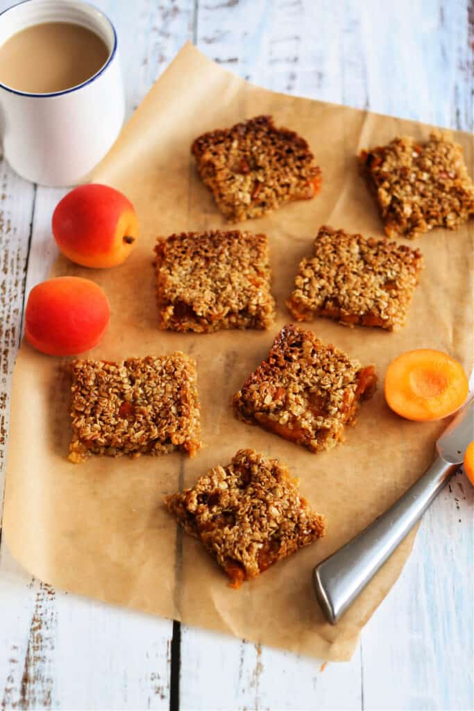 Flapjack pieces on baking paper, with knife, apricots and white cup of tea.