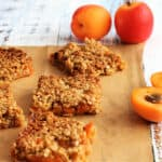 Squares of flapjack on baking parchment with fresh apricots scattered around.