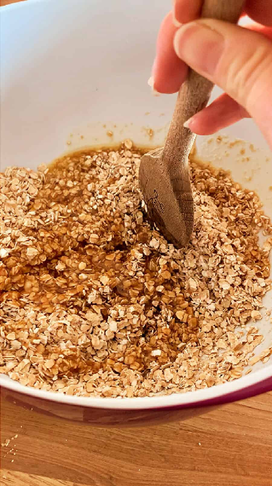 Image showing stirring the butter sugar mixture into oats using a wooden spoon.