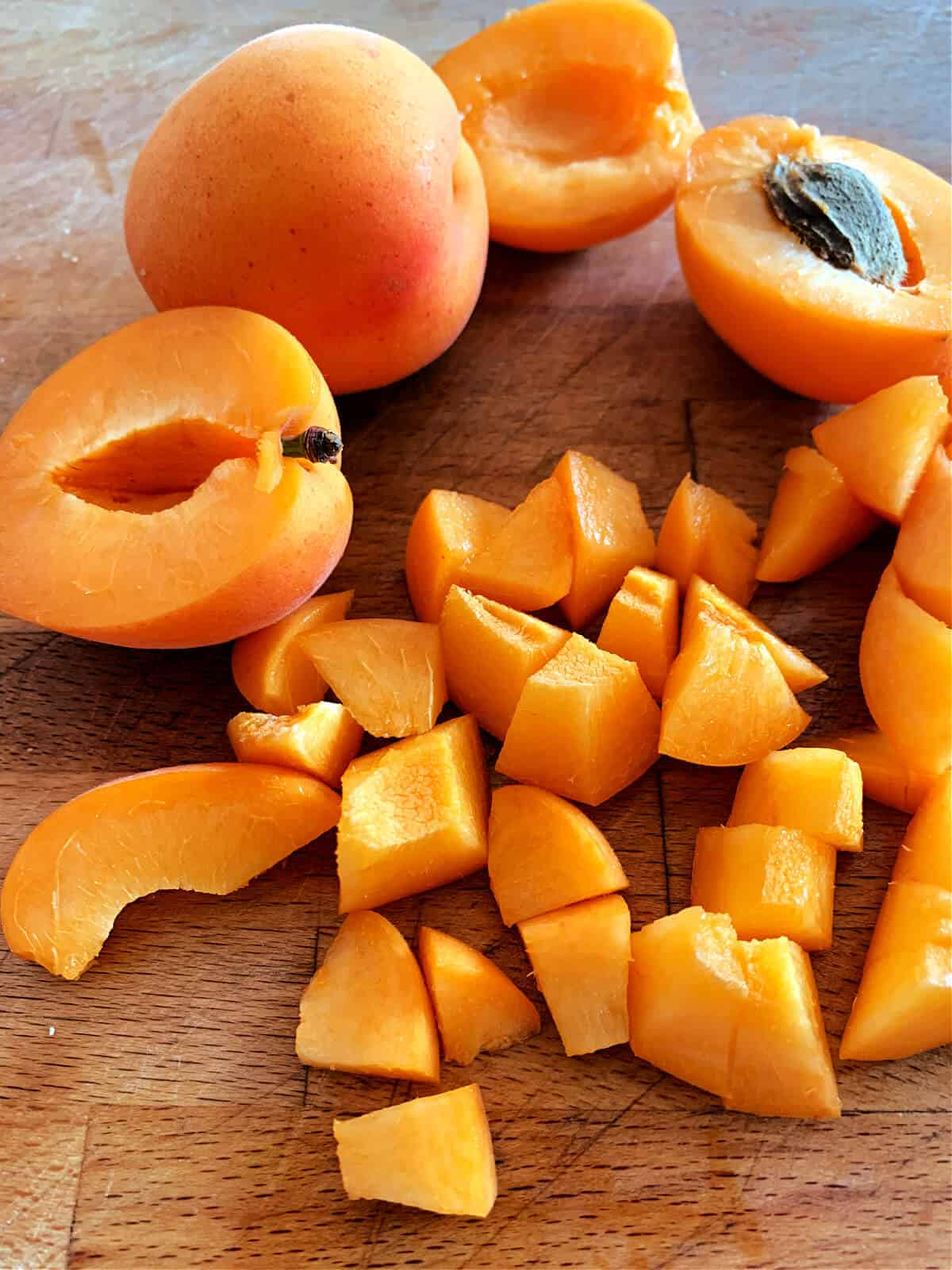 Fresh apricots on a chopping board, some chopped into small pieces, some halved, one whole.