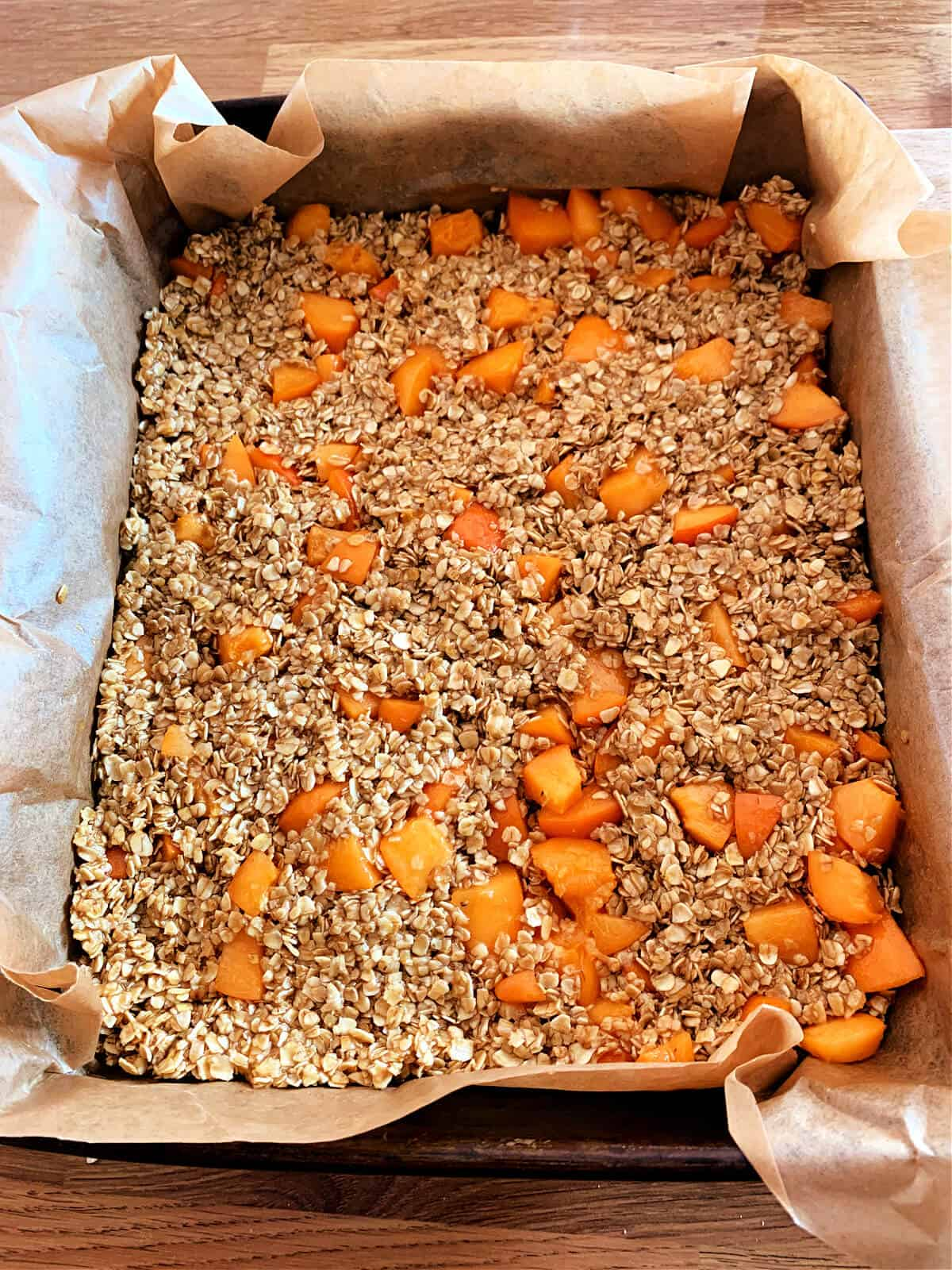 Lined baking tin with apricot flapjack mixture pressed evenly in.