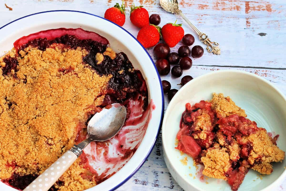 Serving bowl with crumble and a spoon next to a small dish, berry fruits on the table behind.
