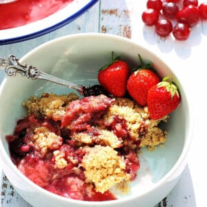 Close up of a bowl of berry crumble with strawberries in a white bowl.