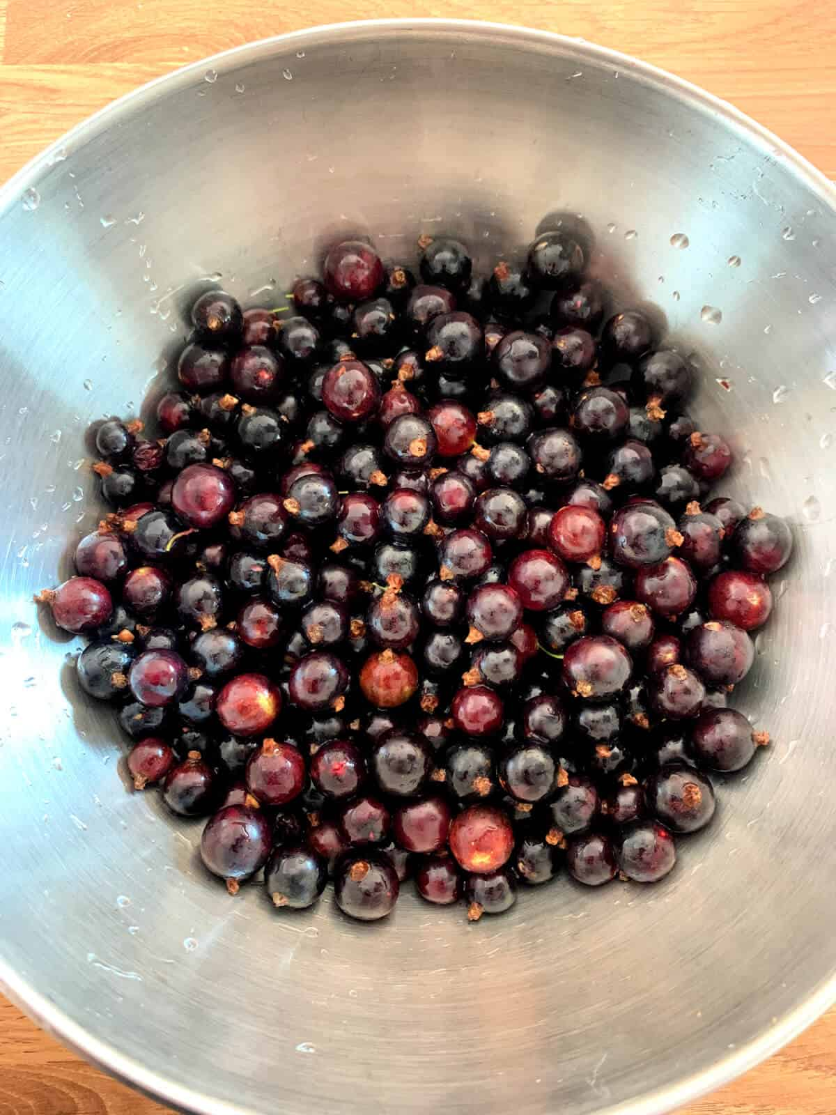 Washed blackcurrants in a metal bowl.